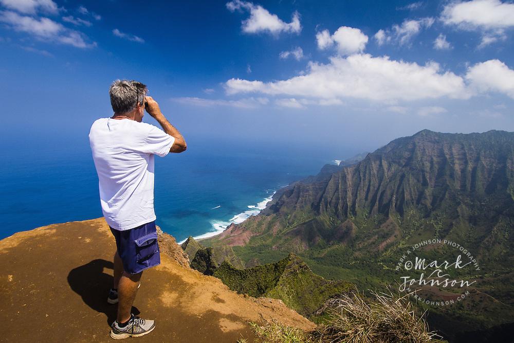 Hiker using binoculars above the Kalalau Valley on the Na Pali Coast, Kokee, Kauai, Hawaii ****Model Release available