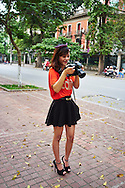 A Vietnamese model looks at the rear screen of a large camera, Hanoi, Vietnam, Southeast Asia
