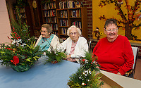 Ida Haddock, Bertha Cote and Judy Holland receive a holiday hand crafted floral arrangement from the Opechee Garden Club on Tuesday afternoon. Approximately 90 arrangements were made by the members of the Opechee Garden Club with a special delivery to the Belknap County Nursing Home.   (Karen Bobotas/for the Laconia Daily Sun)