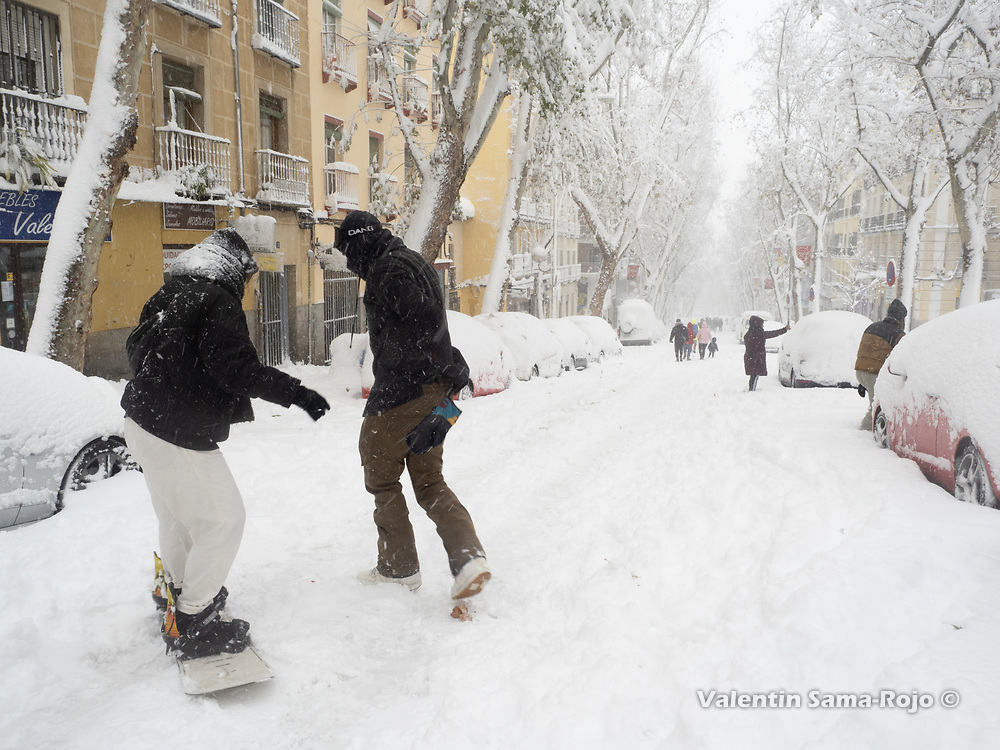 Madrid, Spain. 9 th January, 2021. A person teaching another one how to use a snowboard at Ribera de Curtidores street. Storm Filomena hits Madrid (Spain), a weather alert was issued for cold temperatures and heavy snow storms across Spain; according to the weather agency Aemet is expected to be one of the snowiest days in recent years. © Valentin Sama-Rojo.