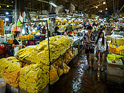 27 FEBRUARY 2019 - BANGKOK, THAILAND:  People walk through Pak Klong Talat, Bangkok's famous flower market. Bangkok, a city of about 14 million, is famous for its raucous nightlife. But Bangkok's real nightlife is seen in its markets and street stalls, many of which are open through the night.         PHOTO BY JACK KURTZ