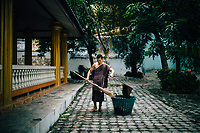 A young monk sweeps the grounds at Tham Krabok temple in Saraburi, Thailand.