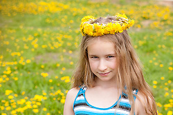 stock photo of a little girl wearing a flower headband made out of dandelions