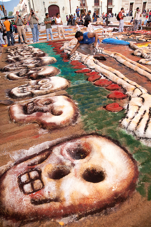 "North America, Mexico, Oaxaca Province, Oaxaca, creation of sand tapestries (Tapetes de Areña) of skulls and skeletons in Zocalo plaza.   These  ""carpets""  are made from sand, dyed sawdust, seeds, flower petals and powdered lime during annual Day of the Dead (Dias de los Muertos) celebration in November"