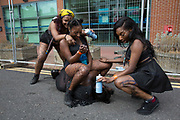 Girls having fun sitting on one another pinning their friends down on Sunday 28th August 2016 at the 50th Notting Hill Carnival in West London. A celebration of West Indian / Caribbean culture and Europes largest street party, festival and parade. Revellers come in their hundreds of thousands to have fun, dance, drink and let go in the brilliant atmosphere. It is led by members of the West Indian / Caribbean community, particularly the Trinidadian and Tobagonian British population, many of whom have lived in the area since the 1950s. The carnival has attracted up to 2 million people in the past and centres around a parade of floats, dancers and sound systems.