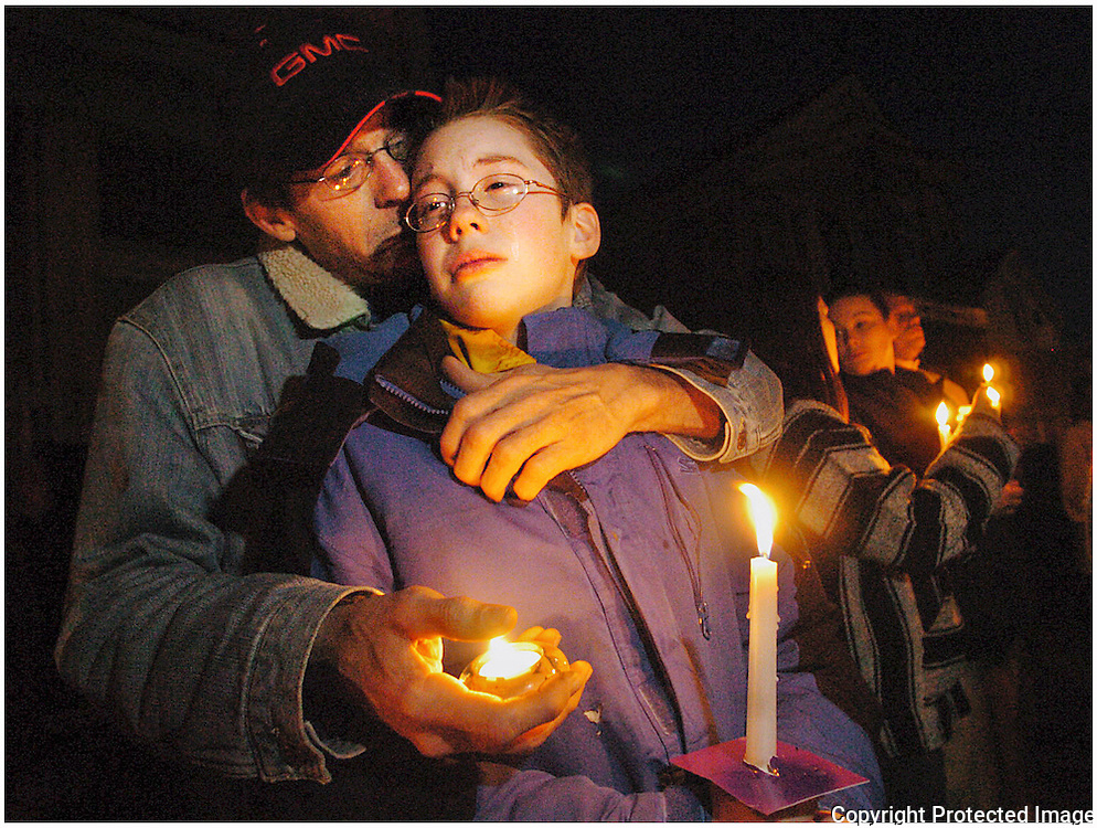 From left, Edward Pohl comforts his 12-year-old son, Tyler Pohl, who becomes emotional at the candlelight vigil held Thursday night for slain Utica police Officer, Thomas Lindsey, on Nielson Street, on the one week anniversary of the day he was shot and killed while making a routine traffic stop, Thursday, April 19, 2007 in Utica.