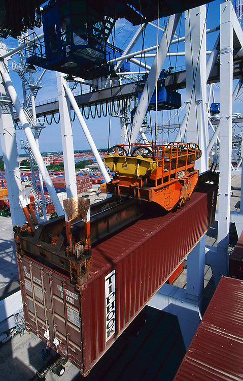 Import containerized freight is offloaded from a container ship and onto waiting trailer trucks at a seaport dock.