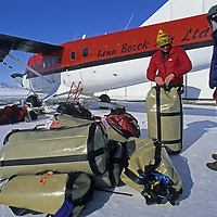BAFFIN ISLAND, NUNAVUT, CANADA. Climbing expedition team loads equipment onto Twin Otter airplane at Iqualuit airport. (Alex Lowe & Mark Synnott)