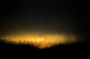 Rays of light illuminate top of trees in surrounding mountains on a stormy morning - Quebec, Canada.