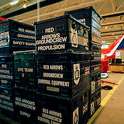 Some crates of flight spares belonging to the 'Red Arrows', Britain's Royal Air Force aerobatic team. Spares and personal effects go into a C-130 Hercules aircraft before the two-day journey from RAF Scampton to RAF Akrotiri in Cyprus. Surrounded by heavy-duty flight-spares, survival equipment boxes and a tyre for a Hawk jet aircraft, the Hercules looms large in the overcast sky. The team complete their winter training schedule in Cyprus. The Red Arrows pilots fly their own jet aircraft to air shows but when requiring the support of ground crew  they borrow a transporter to fly behind the main airborne squadron. 10 tons of spares and personal effects are shipped for a six-week stay.