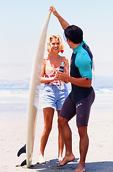 surfer and a beautiful blonde girl at the beach in California