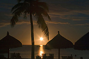Sunrise on Moorea with beach chairs and speedboat in the distance