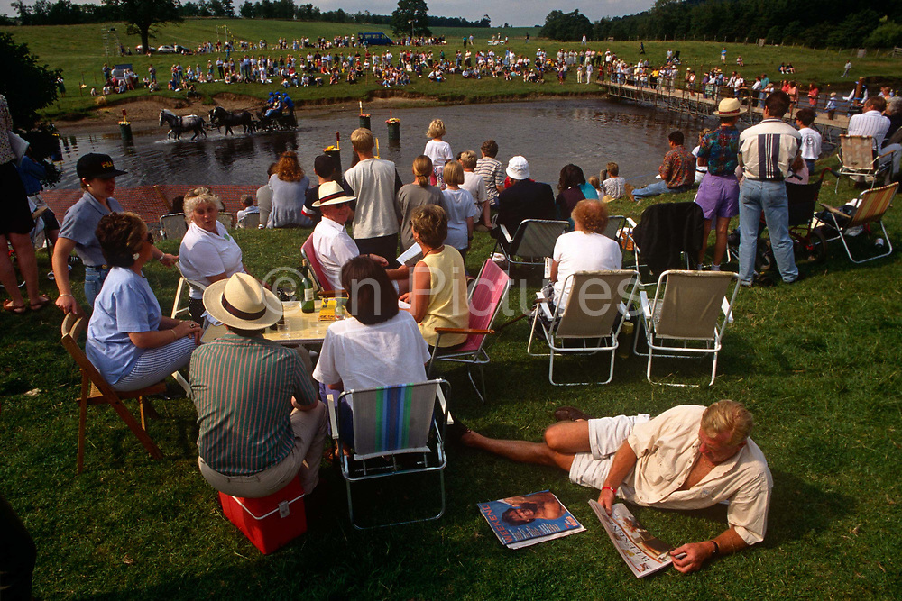 Crowds gather at some water during the annual Carriagedriving trials at the Windsor Great Park Equestrian Club. As one spectator lies across the grass, reading a national newspaper, a competitor negotiates a water feature on the Windsor course. Carriage driving is a form of competitive horse driving in harness in which larger two or four wheeled carriages (often restored antiques) are pulled by a single horse, a pair, tandem or a four-in-hand team. The Windsor Park Equestrian Club is situated among the 5,000 acres of the Windsor Great Park which in turn is part of the 14,000 acre Windsor Estate spanning two counties, Surrey and Berkshire.
