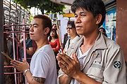 14 OCTOBER 2012 - BANGKOK, THAILAND:   Men pray as a procession passes them in Bangkok's Chinatown on the first day of the Vegetarian Festival. The Vegetarian Festival is celebrated throughout Thailand. It is the Thai version of the The Nine Emperor Gods Festival, a nine-day Taoist celebration beginning on the eve of 9th lunar month of the Chinese calendar. During a period of nine days, those who are participating in the festival dress all in white and abstain from eating meat, poultry, seafood, and dairy products. Vendors and proprietors of restaurants indicate that vegetarian food is for sale by putting a yellow flag out with Thai characters for meatless written on it in red.    PHOTO BY JACK KURTZ