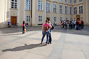 """A couple is doing a """"selfie"""" beside a tourist group in the inner courtyard of Prague Castle. Prague Castle was most likely founded in around 880 by Prince Bořivoj of the Premyslid Dynasty (Přemyslovci). According to the Guinness Book of World Records, Prague Castle is the largest coherent castle complex in the world, with an area of almost 70,000 m². A UNESCO World Heritage site, it consists of a large-scale composition of palaces and ecclesiastical buildings of various architectural styles, from the remains of Romanesque-style buildings from the 10th century through Gothic modifications of the 14th century."""