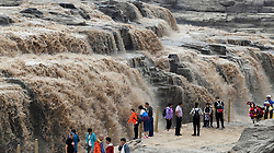 Sept. 4, 2017 - Yan'an, China -  Tourists visit the Hukou Waterfall on the Yellow River on the border area between north China's Shanxi and northwest China's Shaanxi provinces. Due to heavy rainfall at the upper reaches, the water volume of Hukou Waterfall surged. (Credit Image: © Tao Ming/Xinhua via ZUMA Wire)