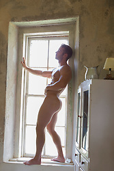 nude bodybuilder standing in a window in a rustic home