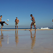 Locals play football on Ipanema beach, Rio de Janeiro, Brazil. 6th July 2010. Photo Tim Clayton..The beaches of Rio de Janeiro, provide the ultimate playground for locals and tourists alike. Beach activity is in abundance as beach volley ball, football and a hybrid of the two, foot volley, are played day and night along the length and breadth of Rio's beaches. .Volleyball nets and football posts stretch along the cities coastline and are a hive of activity particularly at it's most famous beaches Copacabana and Ipanema. .The warm waters of the Atlantic Ocean provide the ideal conditions for a variety of water sports. Walkways along the edge of the beaches along with exercise stations and cycleways encourage sporting activity, even an outdoor gym is available at the Parque Do Arpoador overlooking the ocean. .On Sunday's the main roads along the beaches of Copacabana, Leblon and Ipanema are closed to traffic bringing out thousands of people of all ages to walk, run, jog, ride, skateboard and cycle more than 10 km of beachside roadway. .This sports mad city is about to become a worldwide sporting focus as they play host to the world's biggest sporting events with Brazil hosting the next Fifa World Cup in 2014 and Rio de Janeiro hosting the Olympic Games in 2016..