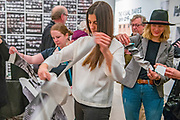"""Portland, Oregon, USA. 26 FEB, 2018. Gallery goers help in shredding the photographer Robert Frank's work printed on newsprint at Blue Sky Gallery in Portland, Oregon, USA. The work was destroyed in a """"Destruction Dance"""" performance defacing the photographs with ink and mutilation with scissors, knives and even ice skates  at the end of it's run. The destruction was Frank's protest regarding today's greed in the global art market."""