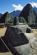 """The four-sided Intihuatana (Hitching Post of the Sun) ritual stone sculpture was likely the most sacred place in Machu Picchu, a magnificent Inca archeological site in the Cordillera Vilcabamba, Andes mountains, Peru, South America. The name Intihuatana (coined perhaps by Hiram Bingham) is derived from the Quechua language: inti means """"sun""""; huata- is a Spanish spelling of wata-, the verb root """"to tie or hitch (up)""""; and the -na suffix derives nouns for tools or places. Scholars dispute various theoretical uses of Intihuatana such as a sacrificial altar, as a temple aligned with the surrounding mountains and their resident apus (gods), as a solar observatory (but unlikely as a sundial), or simply as an abstract art work. The mysterious Intihuatana is an important huaca (or waqa), a revered object, in Quechua language. The stone is at 13°9'48"""" South latitude. Machu Picchu was built around 1450 AD as an estate for the Inca emperor Pachacuti (14381472). Spaniards passed in the river valley below but never discovered Machu Picchu during their conquest of the Incas 1532-1572. The outside world was unaware of the """"Lost City of the Incas"""" until revealed by American historian Hiram Bingham in 1911. Machu Picchu perches at 2430 meters elevation (7970 feet) on a well defended ridge 450 meters (1480 ft) above a loop of the Urubamba/Vilcanota River (Sacred Valley of the Incas). UNESCO honored the Historic Sanctuary of Machu Picchu on the World Heritage List in 1983."""