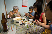Chen Zhen and her family share a meal of greens with garlic, potatoes with green bell pepper, rice, and fava beans with pig's knuckles at their home in Shanghai, China. (From the book What I Eat: Around the World in 80 Diets.)  MODEL RELEASED.