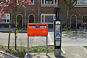 Nederland, Nijmegen, 26-5-2015Een parkeermeter op zonneenergie staat in een wijk vlak buiten het centrum naast een rode brievenbus van de post, postnl.FOTO: FLIP FRANSSEN/ HOLLANDSE HOOGTE