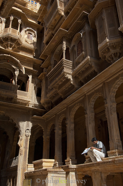 Man reading a newspaper at Jaisalmer Fort, the 'Golden Fort'. It is one of the largest forts in the world. Jaisalmer, Rajasthan, India