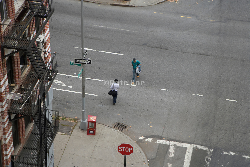 two people crossing a street just before passing each other