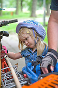 Unhappy Polish girl age 4 resting after bicycle trip. Paderewski Park Rzeczyca Central Poland