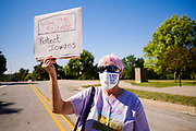 01 AUGUST 2020 - DES MOINES, IOWA: A woman stands on the edge of a gathering of medical doctors calling for a mask mandate at the Iowa State Capitol Saturday. The mask mandate has become a flash point in Iowa. The medical industry, educators , students and many others support a mask mandate. Republicans do not. About 50 doctors, medical professionals, and public health professionals from across Iowa came to the State Capitol to demand that Iowa Governor Kim Reynolds impose a mask mandate to control the spread of the coronavirus (SARS-CoV-2). Despite the continued spread of the coronavirus and rapidly increasing infection rate for COVID-19, the Governor has refused to impose a mask mandate or close businesses. For the week ending Saturday, Aug. 1, Iowa reported new 2,736 new cases of COVID-19.             PHOTO BY JACK KURTZ