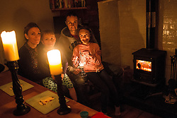 © Licensed to London News Pictures . 24/03/2013 . L-R Mum Lindsay Hassan (37) , Son Elliot Barrett (5) , Dad Paul Barrett (42) and Daughter Lucie Barrett (9) of 35 Saxby Street , Salford , stay warm by their real fire and use candles to light their living room . A power cut in Salford this evening (24th March) has left dozens of homes without power in freezing temperatures . Photo credit : Joel Goodman/LNP
