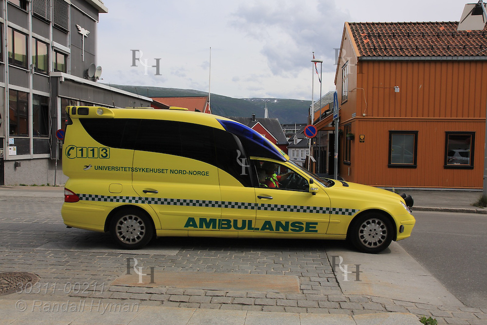 Yellow ambulance drives down street in downtown Tromso, Norway.