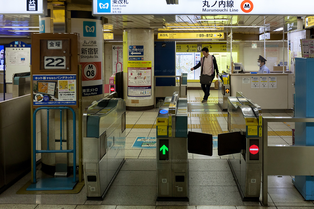 A station worker sits behind a makeshift plastic screen to guard  against infection with the Coronavirus  in Shinjuku station,, Tokyo, Japan. Friday May 22nd 2020.. The two-month long state of emergency  declared by the Japanese government in response to the COVID-19 pandemic  is slated to end on May 25th Despite Japan appearing to have avoided the high infection and mortality rates of some countries. Areas in Tokyo and across the country have many businesses shuttered and closed and the streets are a lot quieter than usual.
