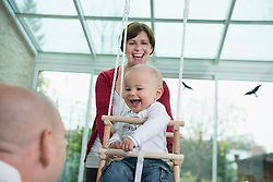 Happy toddler sitting in a swing