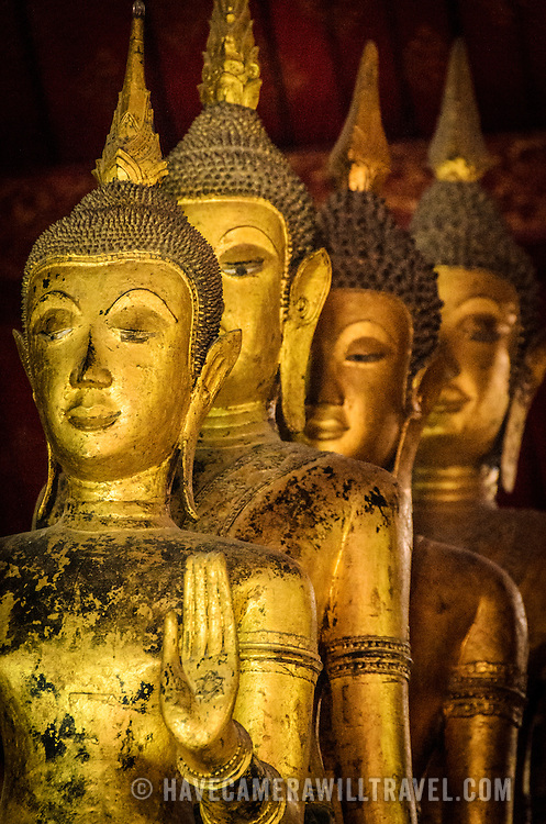 A line of gold Buddha statues at Wat Mai Suwannaphumaham.  Wat Mai, as it is often known, is a Buddhist temple in Luang Prabang, Laos, located near the Royal Palace Museum. It was built in the 18th century and is one of the most richly decorated Wats in Luang Prabang.