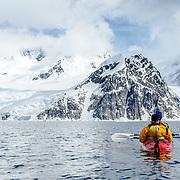 Kayakers in a tandem sea kayak head towards a steep rocky mountain at Neko Harbour, Antarctica.