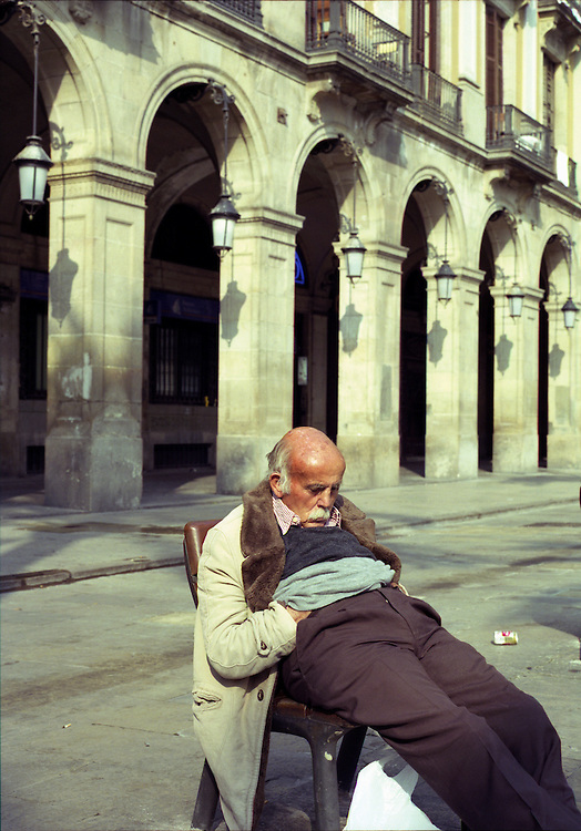 A man asleep in the Placa Real, Barcelona. Spain 2003.