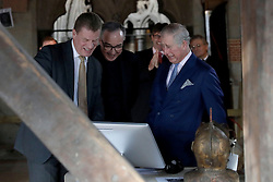 The Prince of Wales is shown a slide on a screen on a table of artefacts by Dr Tony Trowles (left) the head of collections, flanked by the Dean of Westminster John Hall during his visit to the The Queen's Diamond Jubilee Galleries at Westminster Abbey in London.