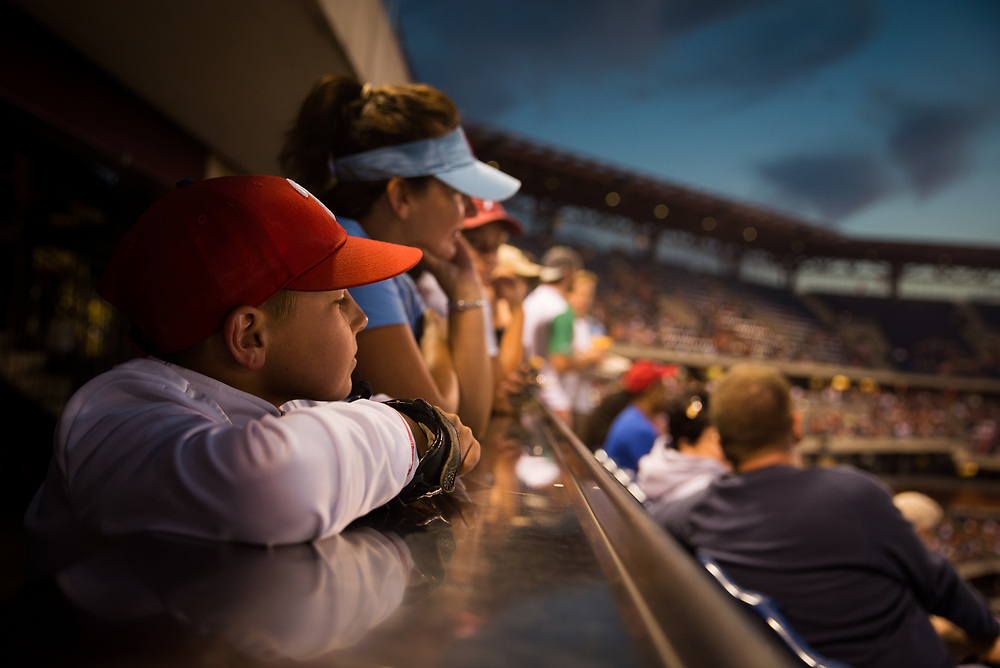 """Gavin Sheetz, 10, with his mother Yvette Sheetz, 43, watch the Phillies in action. The Sheetz family comes to games from Reading, PA, two or three times a year, and more often go to Reading Phillies games, and wait for minor league prospects to crop up at Citizens Bank Park. """"It seems like every time we make the trek they lose badly, and then they win big the next day,"""" Gavin said."""