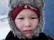 Jakutischer Junge mit Kopfbedeckung geschützt gegen die extreme Kaelte in der Innenstadt von Jakutsk. Jakutsk wurde 1632 gegruendet und feierte 2007 sein 375 jaehriges Bestehen. Jakutsk ist im Winter eine der kaeltesten Grossstaedte weltweit mit durchschnittlichen Winter Temperaturen von -40.9 Grad Celsius. Die Stadt ist nicht weit entfernt von Oimjakon, dem Kaeltepol der bewohnten Gebiete der Erde.<br /> <br /> Yakut boy protected with headgears against the extrem climate  in the city center of Yakutsk. Yakutsk was founded in 1632 and celebrated 2007 the 375th anniversary - billboard announcing the celebration. Yakutsk is a city in the Russian Far East, located about 4 degrees (450 km) below the Arctic Circle. It is the capital of the Sakha (Yakutia) Republic (formerly the Yakut Autonomous Soviet Socialist Republic), Russia and a major port on the Lena River. Yakutsk is one of the coldest cities on earth, with winter temperatures averaging -40.9 degrees Celsius.