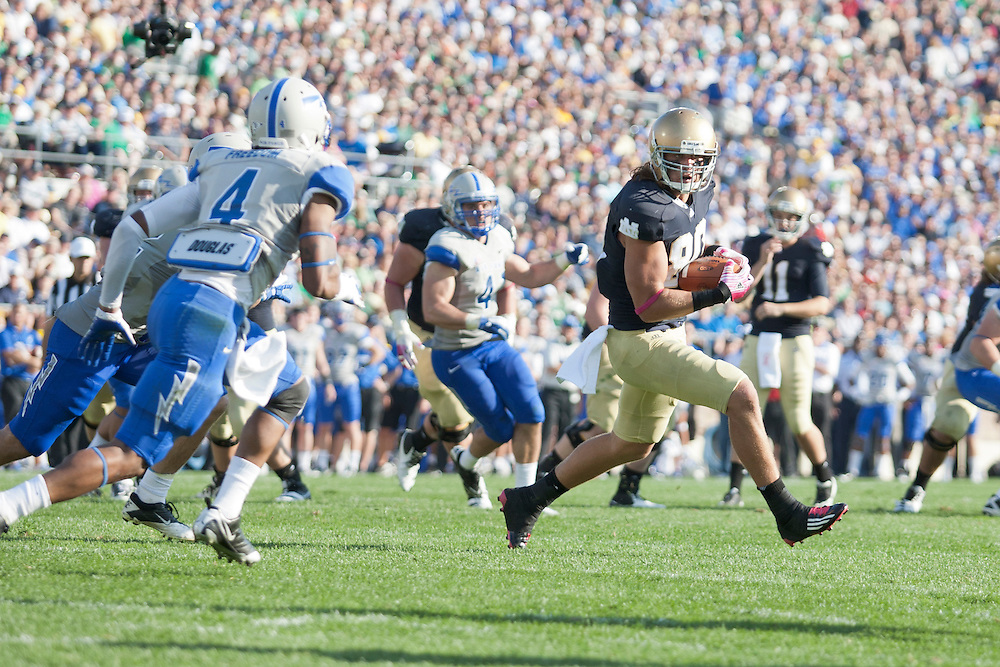 Notre Dame tight end Tyler Eifert (#80) runs for yardage after the catch as Air Force defensive back Anthony Wooding Jr. (#4) defends in action during NCAA football game between Notre Dame and Air Force.  The Notre Dame Fighting Irish defeated the Air Force Falcons 59-33 in game at Notre Dame Stadium in South Bend, Indiana.