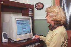 Woman sitting at desk using computer at home,