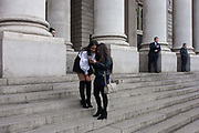 Two laughing young women pause to admire their photos on the steps of Royal Exchange, on 9th December 2016, in the City of London, England.