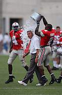 Former Ohio State player Mike Doss, right, dumps a bucket of water on the head of head coach Jim Tressel after the Buckeyes' win over Washington State last season. Chris Vance is in the background.