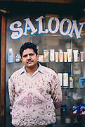 A barber shop owner stands outside his salon in central Delhi. Hair from the barber shops is swept up and then sent off to the hair processing factories. This hair has a variety of uses ranging from stuffing for jackets, cosmetic brushes as well as the extraction of the amino acids within the hair which can be used in food and medicine.