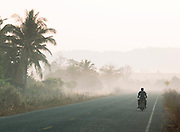Locals on mopeds driving through rural countryside, Siem Reap Province, Cambodia