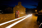 Public phone box and car headlights in a street at New Lanark, the industrial revolution community village managed by social pioneer Robert Owen. New Lanark is on the River Clyde, approximately 1.4 miles (2.2 kilometres) from Lanark, in South Lanarkshire, Scotland. It was founded in 1786 by David Dale, who built cotton mills  and housing for the mill workers. Dale built the mills there to take advantage of the water power provided by the river. Under the ownership of a partnership that included Dale's son-in-law, Robert Owen, a Welsh philanthropist and social reformer, New Lanark became a successful business and an epitome of utopian socialism. The New Lanark mills operated until 1968 and is now one of five UNESCO World Heritage Sites in Scotland.