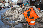 A bright orange road work sign warning people of traffic road works in front of a large pile of snow on East Houston Street in Lower East Side, New York City, New York, Unites States of America.  In January 2016 the city experienced a record breaking snowstorm.