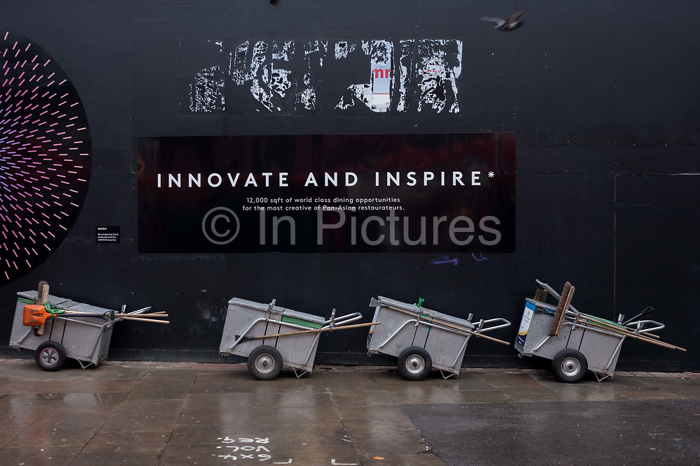 A dystopian landscape of Westminster council sweepers barrows and an inspirational corporate slogan on a construction hoarding, on 31st January 2017, in Chinatown, London, England.