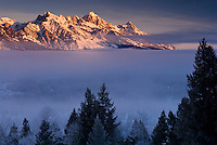 The high peaks of the Tetons tower over a valley fog layer at sunrise in Jackson Hole, Wyoming.